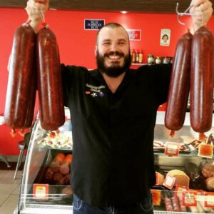 Robin holding up a range of our BLackforest salamis